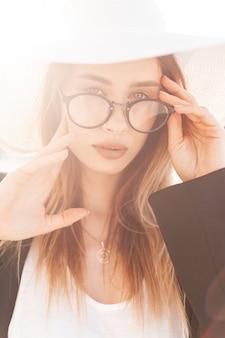 Mulher jovem e bonita com um chapéu de praia com óculos e uma jaqueta preta com uma camiseta branca ao pôr do sol. garota muito elegante com roupas de verão em dia ensolarado