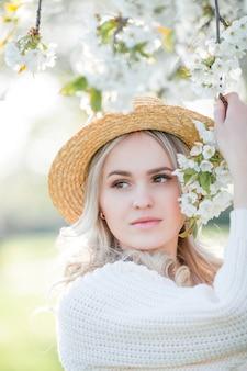 Mulher jovem e bonita com um chapéu de vime descansando em um piquenique em um jardim florido