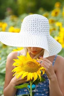 Mulher jovem e bonita com um chapéu e óculos em um campo de girassóis.