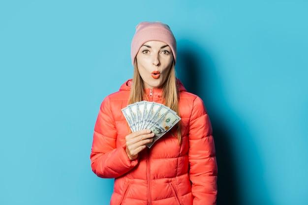 Mulher jovem e bonita com um chapéu e uma jaqueta de inverno com uma cara surpresa segurando dinheiro