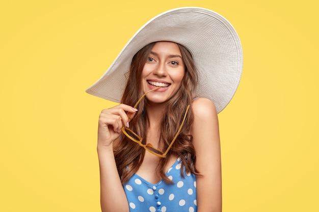 Mulher jovem e bonita com um chapéu posando contra a parede amarela