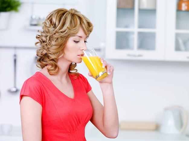 Mulher jovem e bonita com um copo de suco de laranja fresco na cozinha