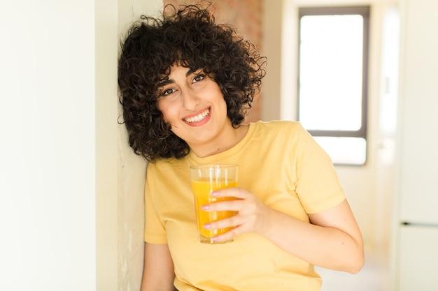 Mulher jovem e bonita com um copo de suco de laranja