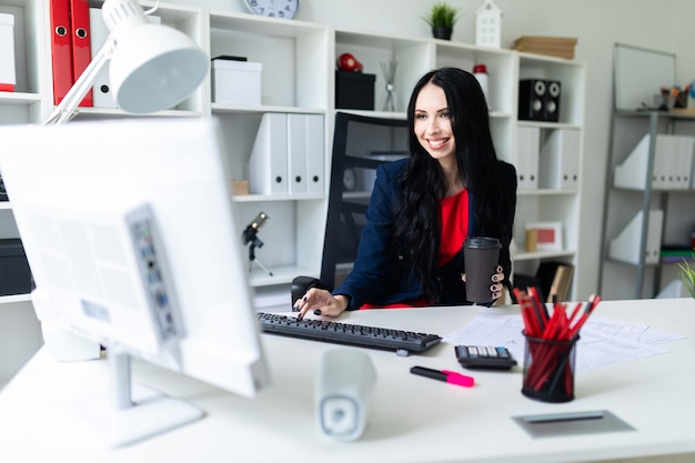 Mulher jovem e bonita com um copo na mão com café e digitando o texto no teclado, sentado em uma cadeira no escritório à mesa.