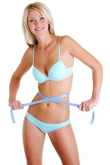 Mulher jovem e bonita com um corpo de saúde de beleza com fita métrica. vista frontal sobre branco.