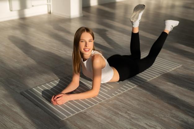 Mulher jovem e bonita com um corpo esguio está envolvida na ginástica
