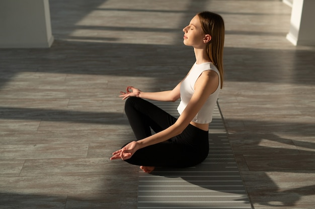 Mulher jovem e bonita com um corpo esguio praticando ioga no corredor