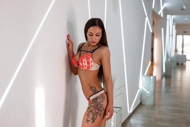 Mulher jovem e bonita com um corpo tatuado em lingerie perto de uma parede com luz