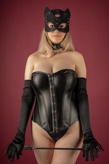Mulher jovem e bonita com um espartilho de couro e máscara de gato posando com um chicote nas mãos