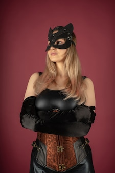 Mulher jovem e bonita com um espartilho de couro e máscara de gato posando