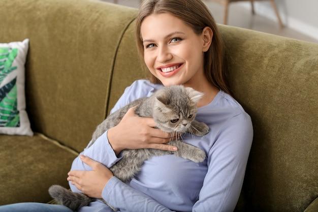 Mulher jovem e bonita com um gato fofo em casa