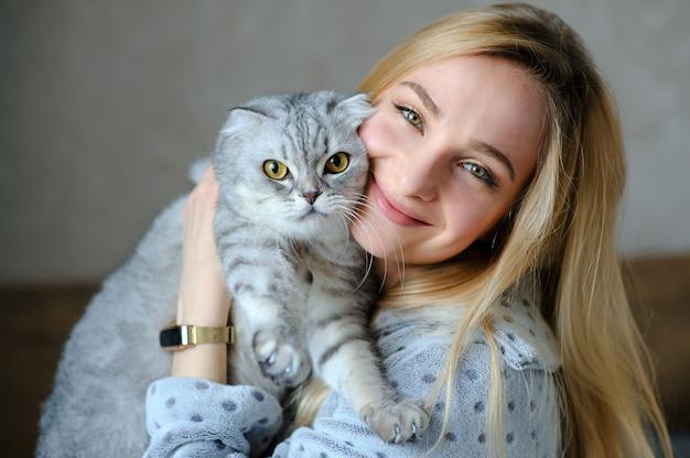 Mulher jovem e bonita com um gato fofo na cama