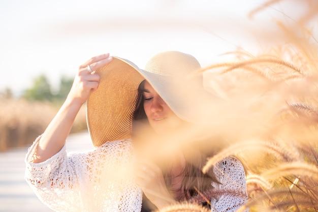Mulher jovem e bonita com um grande chapéu entre a grama do campo close-up.