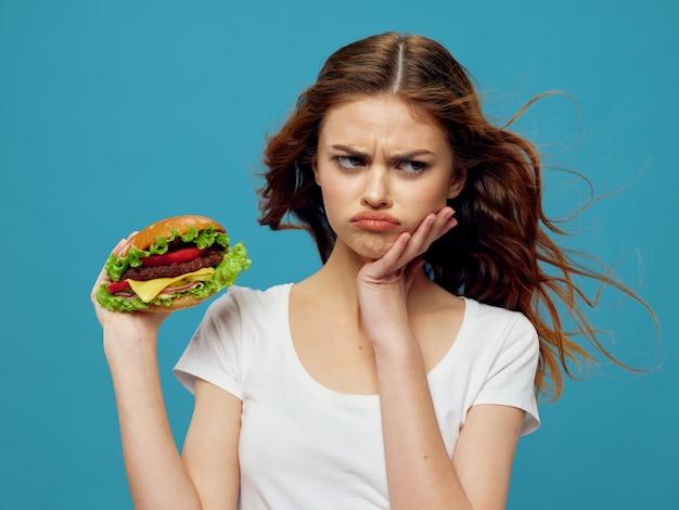 Mulher jovem e bonita com um hambúrguer suculento nas mãos, uma mulher comendo um hambúrguer