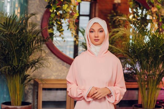 Mulher jovem e bonita com um hijab rosa.