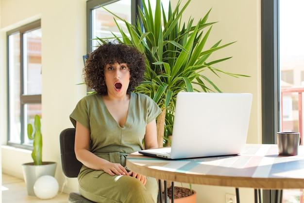 Mulher jovem e bonita com um laptop sobre uma mesa