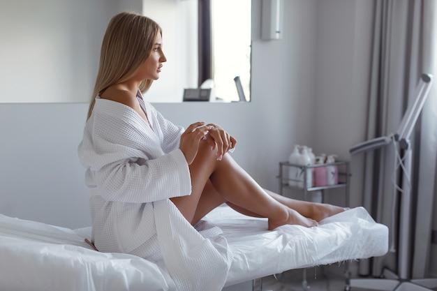 Mulher jovem e bonita com um manto branco aplica creme hidratante nas mãos, sentada no sofá em um salão de beleza. spa.
