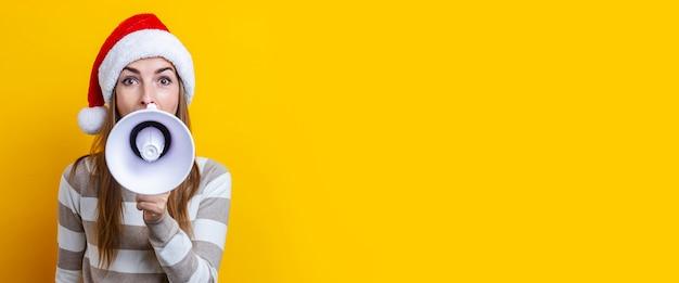 Mulher jovem e bonita com um megafone em um fundo amarelo. bandeira.