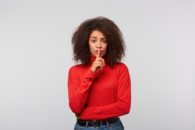 Mulher jovem e bonita com um penteado afro com um segredo, segurando o dedo nos lábios e mostrando o sinal de silêncio