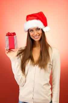 Mulher jovem e bonita com um presente, sobre fundo vermelho