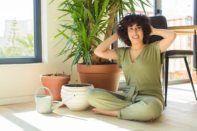 Mulher jovem e bonita com um regador e plantas