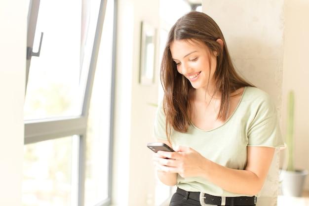 Mulher jovem e bonita com um smartphone em casa