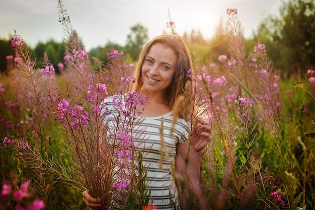 Mulher jovem e bonita com um sorriso feliz, agarrando-se ao alto hastes erva kipray
