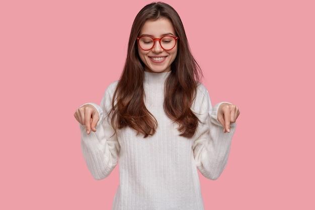Mulher jovem e bonita com um sorriso terno apontando para baixo com os dois dedos indicadores, mostrando os sapatos novos que comprou