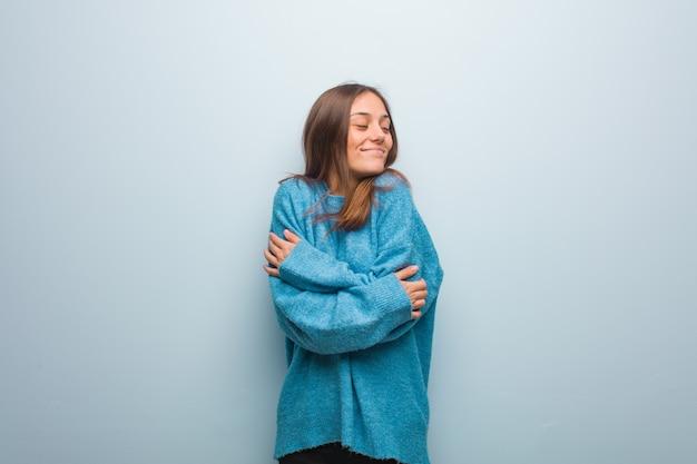 Mulher jovem e bonita com um suéter azul dando um abraço