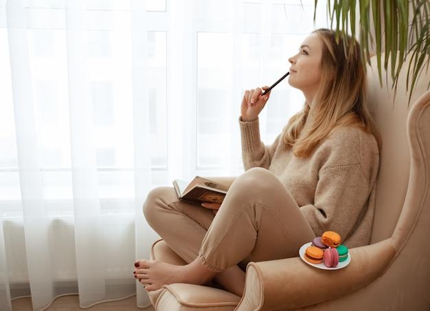 Mulher jovem e bonita com um suéter bege na cadeira perto da janela em casa com olhar pensativo e pensativo