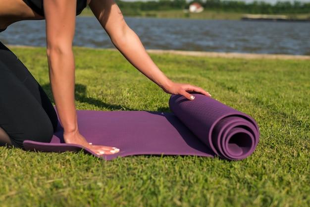 Mulher jovem e bonita com um tapete de ioga ao ar livre.