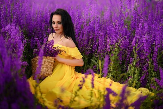 Mulher jovem e bonita com um vestido amarelo se senta em um campo de flores roxas.