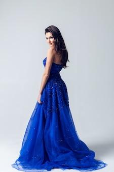 Mulher jovem e bonita com um vestido azul escuro sobre uma parede cinza clara