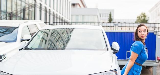 Mulher jovem e bonita com um vestido azul posando perto do carro