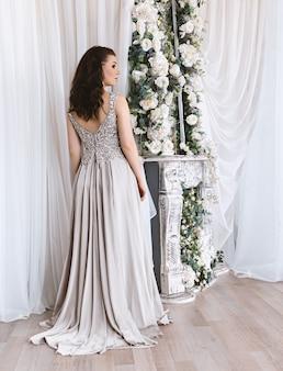 Mulher jovem e bonita com um vestido branco romântico em pé perto de espelho decorado com flores brancas.