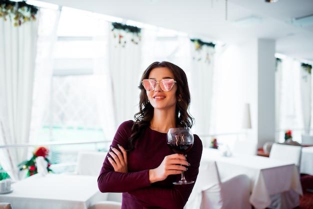 Mulher jovem e bonita com um vestido cinza fica com um copo de vinho nas mãos no fundo da árvore de natal, luzes e guirlandas.