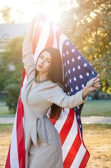 Mulher jovem e bonita com um vestido clássico segurando a bandeira americana no parque.