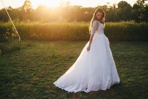 Mulher jovem e bonita com um vestido de casamento branco e botas pretas ao pôr do sol.