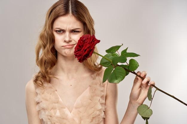 Mulher jovem e bonita com um vestido delicado com uma rosa escarlate na mão, um feriado e um presente