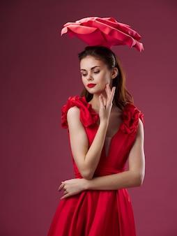 Mulher jovem e bonita com um vestido luxuoso com rosas, pétalas de rosa, batom vermelho, imagem elegante