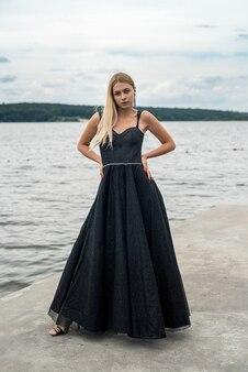 Mulher jovem e bonita com um vestido preto longo de noite perto da lagoa, estilo de vida de verão