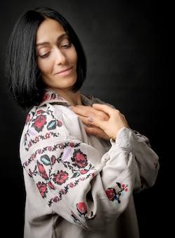 Mulher jovem e bonita com um vestido ucraniano antigo bordado com um ponto de cruz no preto