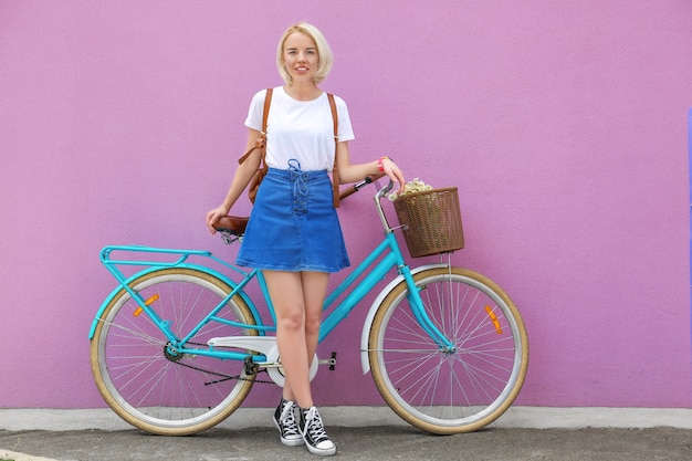 Mulher jovem e bonita com uma bicicleta estilosa em pé perto da parede colorida