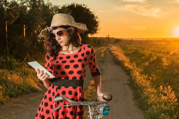 Mulher jovem e bonita com uma bicicleta lendo e-mails em seu tablet ao ar livre