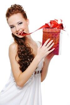 Mulher jovem e bonita com uma caixa vermelha nos braços morder levemente a fita e desenhá-la