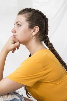Mulher jovem e bonita com uma camisa amarela e cabelo trançado sentada contra uma parede branca