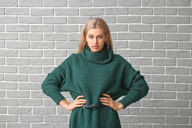 Mulher jovem e bonita com uma camisola quente em fundo de tijolo