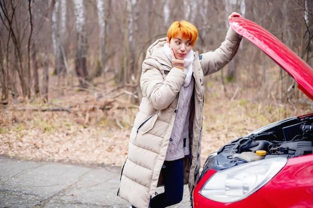 Mulher jovem e bonita com uma expressão de surpresa olha para o capô aberto do compartimento do motor de um carro vermelho no fundo da floresta, garota ao lado de um carro quebrado