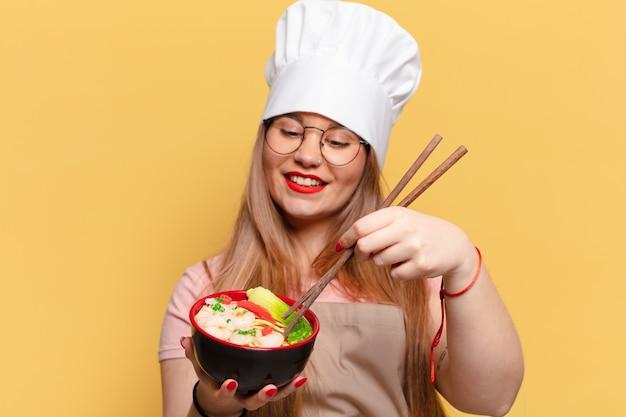 Mulher jovem e bonita com uma expressão feliz e surpresa cozinhando macarrão