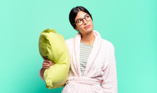 Mulher jovem e bonita com uma expressão preocupada, confusa e sem noção, olhando para cima para copiar o espaço, em dúvida. conceito de pijama